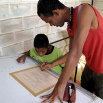 Dedê Galdino Santana helps a young student with his drawing.