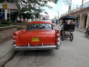 Chevvies, Oldsmobiles and Studebakers share the road with horse buggies and bullock carts.